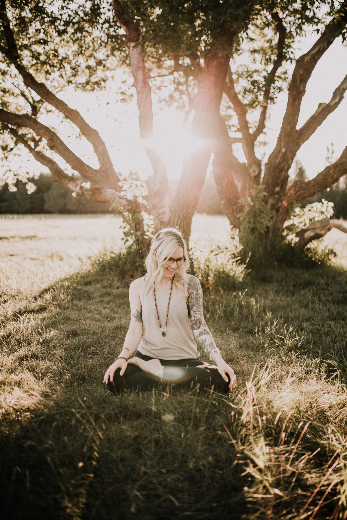 Woman sitting in yoga pose at sunset outside